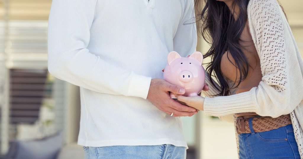 Couple holding a piggy bank in their new home. Home savings concept. They are standing in front of the their new modern house. Both are happy and smiling.