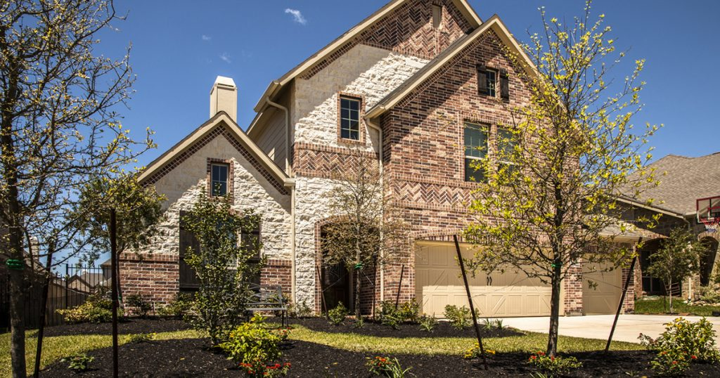 Exterior facade of two-story brick and stone home in residential neighborhood. Landscaped front yard, three-car garage.