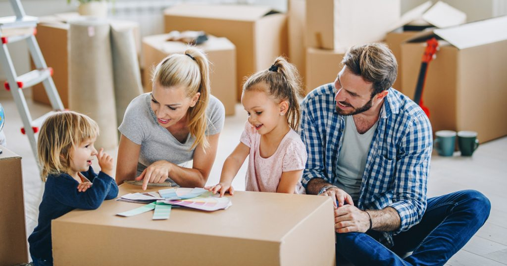 Young happy family moving in new home and choosing colors form palette.