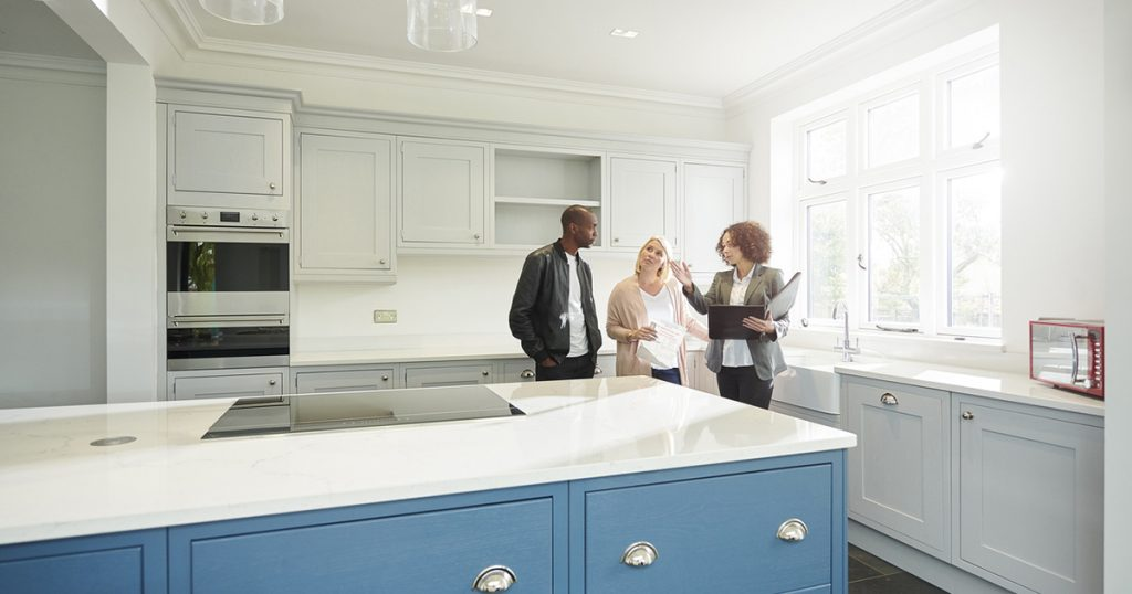 saleswoman or estate agent shows a couple around a home with new kitchen